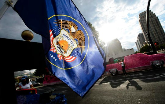 """FILE - In this July 24, 2017, file photo the Utah state flag waves in the morning sun at the start of the Days of '47 Parade in Salt Lake City. A Utah state lawmaker is leading an effort to redesign a clunky Utah state flag that critics have called an """"S.O.B."""", seal on a bedsheet. State Rep. Steve Handy recently announced he will introduce a bill creating a flag review commission that could ultimately scrap the turbulent form of the 100-year-old flag for a new, simpler one, The Salt Lake Tribune reports . (Steve Griffin/The Salt Lake Tribune via AP, File)"""