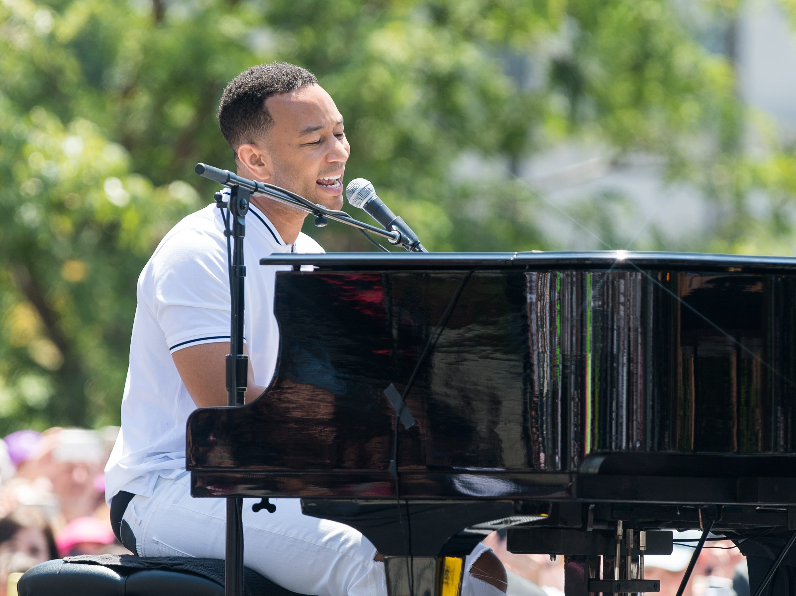 """June 30: At a sister """"Families Belong Together"""" march in Los Angeles, John Legend performs onstage."""