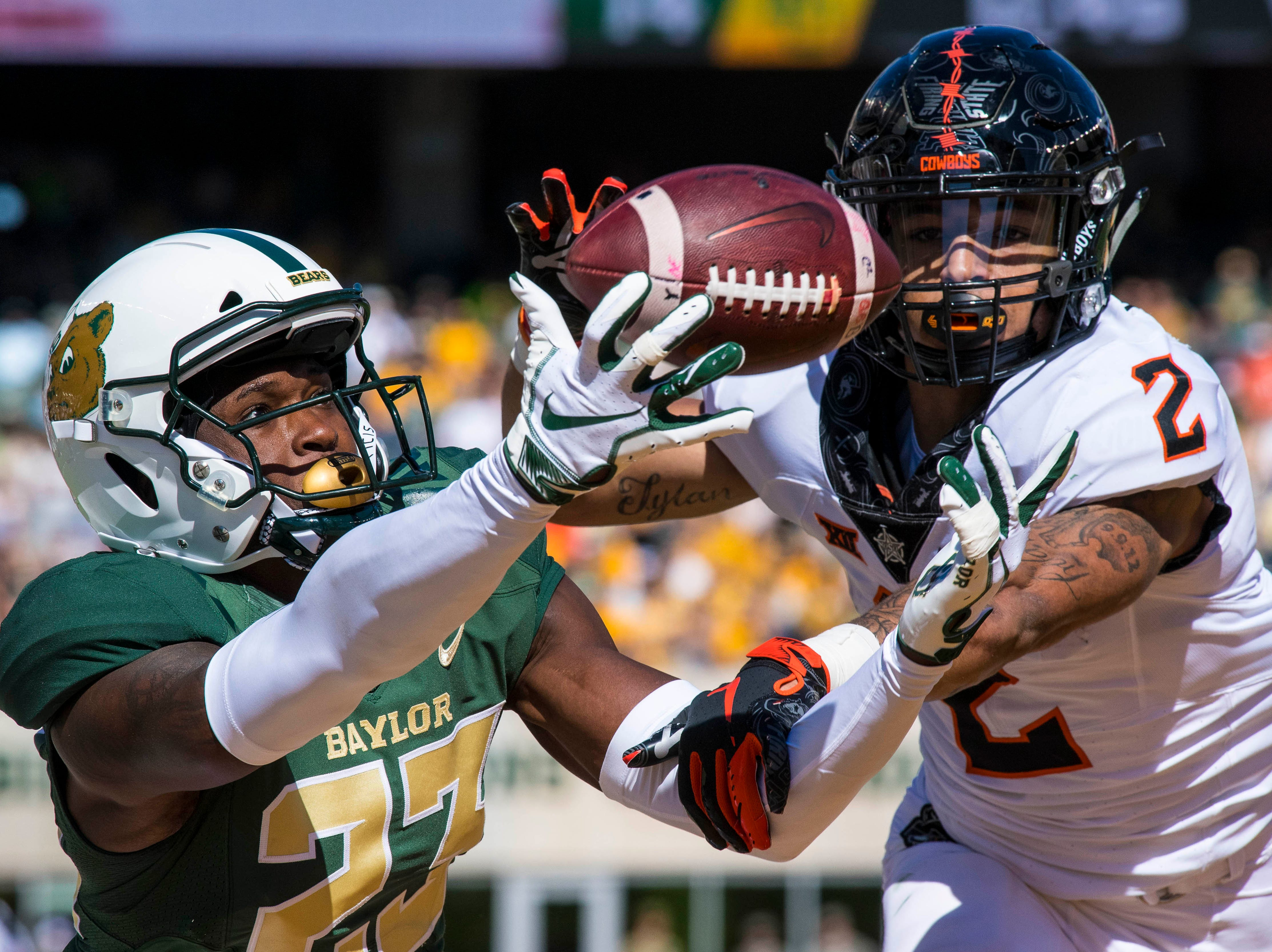Nov. 3: Baylor Bears cornerback Derrek Thomas (23) and Oklahoma State Cowboys wide receiver Tylan Wallace (2) fight for the ball during the first half at McLane Stadium.