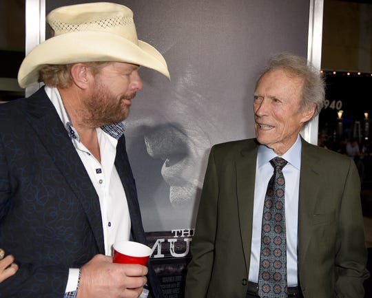 """Toby Keith, left, and Clint Eastwood arrive Dec. 10, 2018, at the premiere of """"The Mule"""" at the Village Theatre in Los Angeles."""