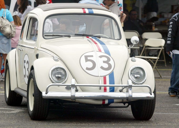 """IRVINE, CA - JUNE 12: Visitors get a look at some privately owned replicas of """"Herbie"""", as well as two of the cars that were used in the film """"Herbie Fully Loaded"""" at Verizon Wireless Amphitheatre on June 12, 2005 in Irvine, California. Herbie is the theme of this years VW Classic. (Photo by Matthew Simmons/Getty Images)"""