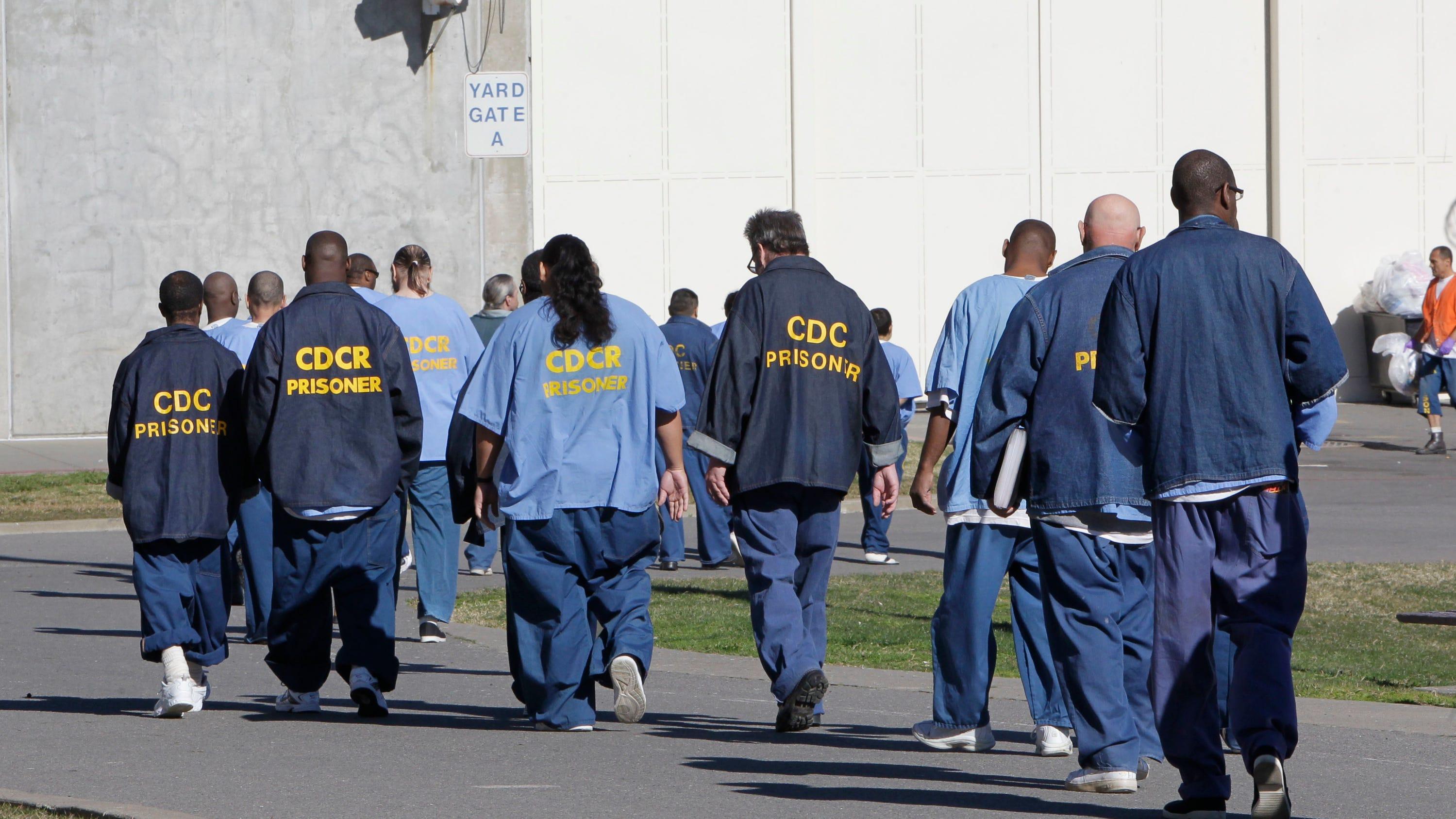 Inmates walk through the exercise yard at California State Prison Sacramento, near Folsom, Calif.