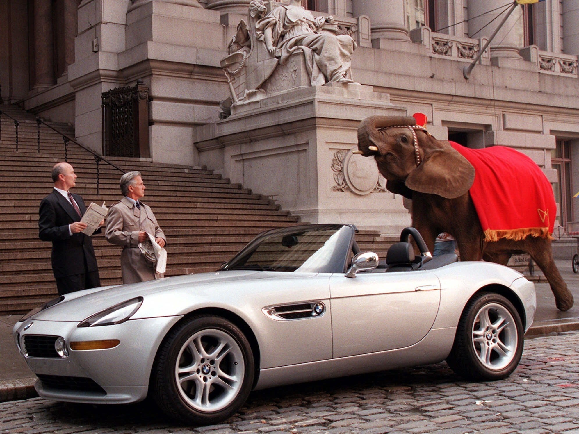 """A downtown Manhattan street is transformed Sunday, Aug. 29, 1999, into a European setting, fully equipped for a car commercial with spies, an elephant, and the new BMW Z8, the car featured in the James Bond movie """"The World is Not Enough,"""" which will be released in theaters nationwide in November. Amy the elephant and actors Ed Hyland, left, and Dennis Parlato film a take for a commercial being released spring 2000 in North America, featuring the new BMW Z8.  (AP Photo/BMW, Stuart Ramson) ORG XMIT: NYR105 [Via MerlinFTP Drop]"""