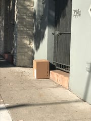 A package delivered to a home in and left in front of the door.