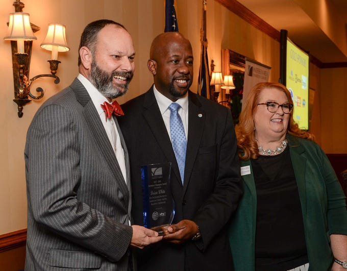 Terrance Ford, middle, AT&T Director of Legislative Affairs, presents State Rep. Brian White the 2017-2018 Business Champion Award near President and CEO Pamela Christopher, right, of the Anderson Area Chamber of Commerce, during the chamber lunch at Tucker's in Anderson Thursday, December 13, 2018.