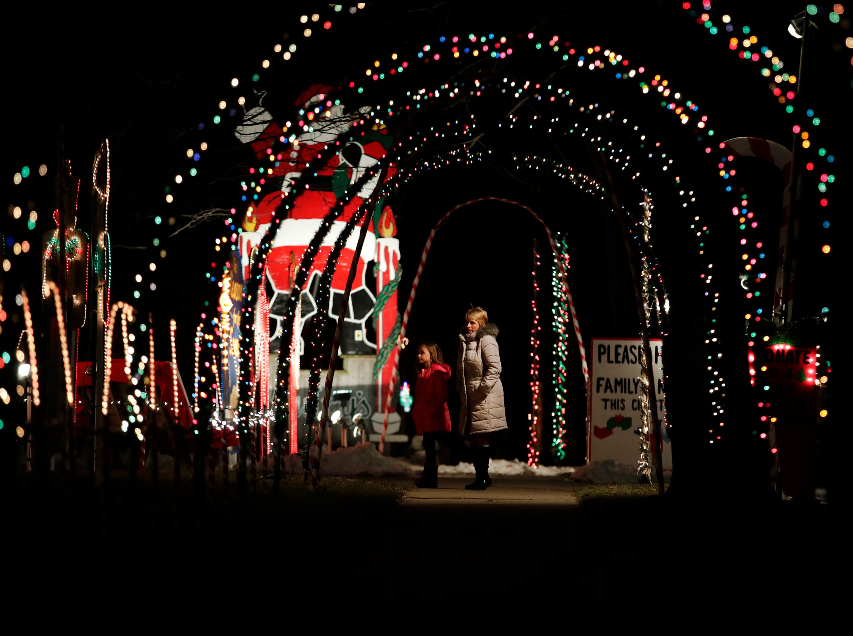 Jody Hilley, of Appleton, and her granddaughter Natalie Du Bois, 9, of Kaukauna walk through a tunnel of Christmas lights on the 500 block of Janssen Street Wednesday Dec. 5, 2018, in Combined Locks, Wis.