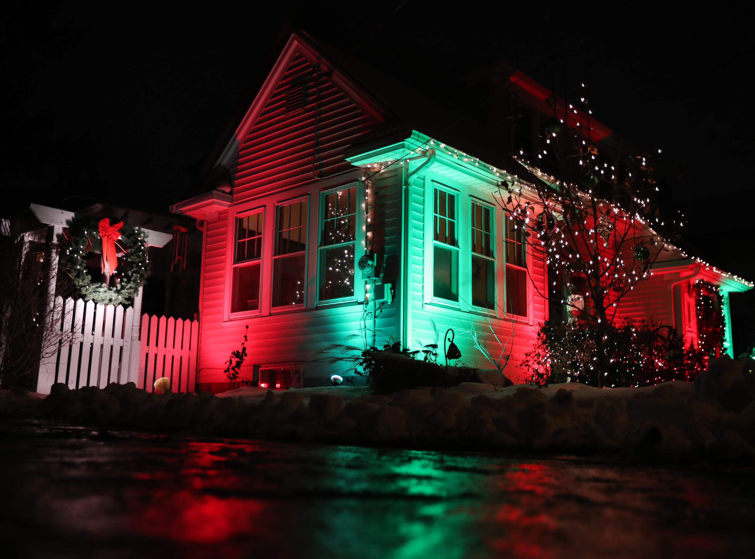 A home on the 200 block of East Circle Street is lit up by red and green lights Wednesday Dec. 5, 2018, in Appleton, Wis.
