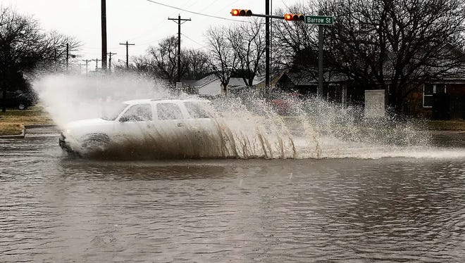 A vehicle splashes its way across an intersection Thursday afternoon as cold rain fell in Abilene and temperatures slowly dropped. Wintry weather was expected after sundown.