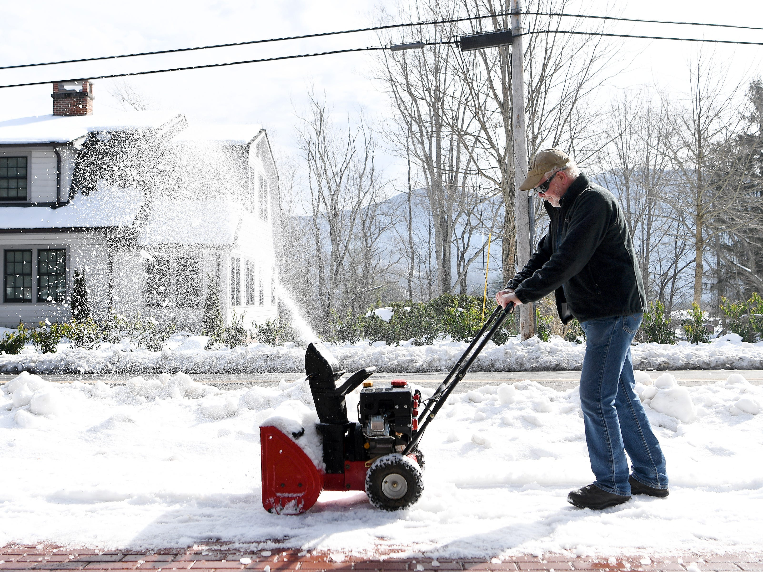 Rick Gordon, owner of the Oak Park Inn in Waynesville, uses a snowblower on the sidewalk in front of Kandi's Cakes and Bake Shop so the sun could melt the rest of the ice on Dec. 12, 2018.