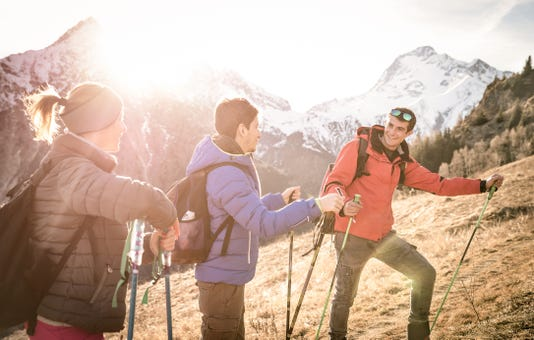 Group Of Friends Trekking On French Alps At Sunset Hikers With Backpacks And Sticks Walking On Mountain Wanderlust Travel Concept With Young People At Excursion In Wild Nature Focus On Right Guy