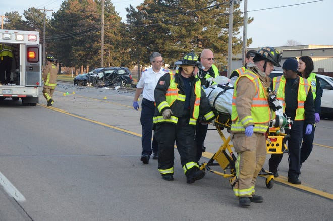 First responders take a woman to a waiting medical helicopter following a crash Thursday on Dickman Road.