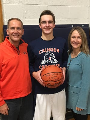Calhoun Christian's Alex Wilcox shows off the game ball that he scored his 1,000th career point with. He is joined by his parents, Dave and Amy Wilcox.
