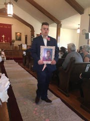 Krista Acker Ellsworth's Man of Honor, Nick Moran, carries a photo of Krista's Maid of Honor, her sister, Allison, who died when she was 9.