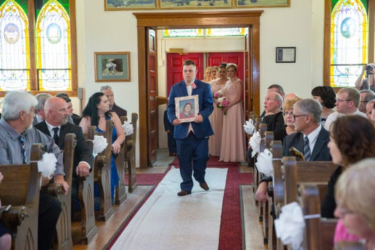 Nick Moran carries a photograph of Krista Ellsworth's sister, Allison, who died at the age of 9, during Krista's wedding.