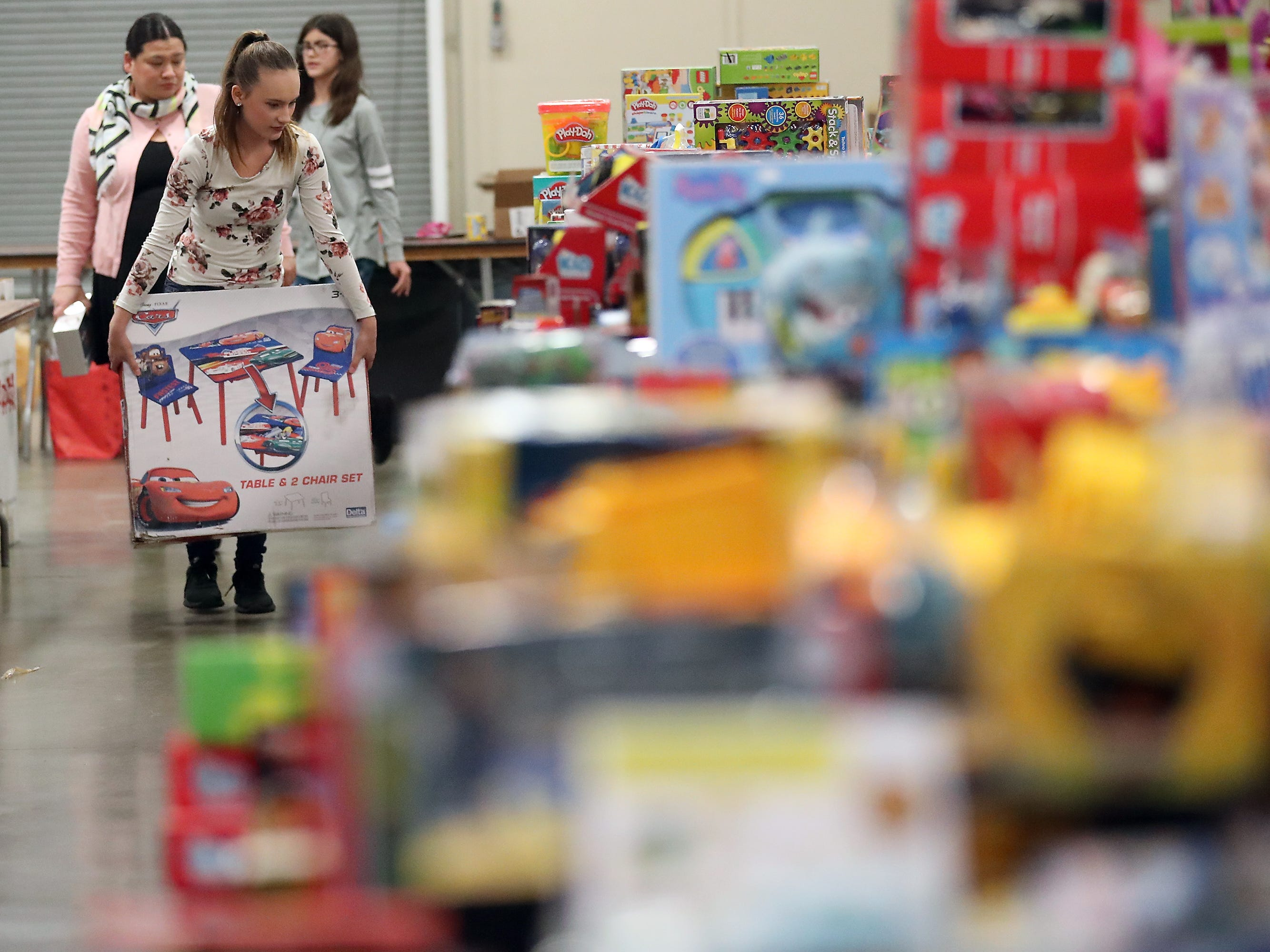 Volunteer Mikayla Hawk, 14, makes her way along the tables of toys as she tries to find a spot for a large item for the upcoming Toys For Tots event in President's Hall at the Kitsap County Fairgrounds on Wednesday, December 12, 2018. This is the second year that Mikayla has been volunteering at the event.