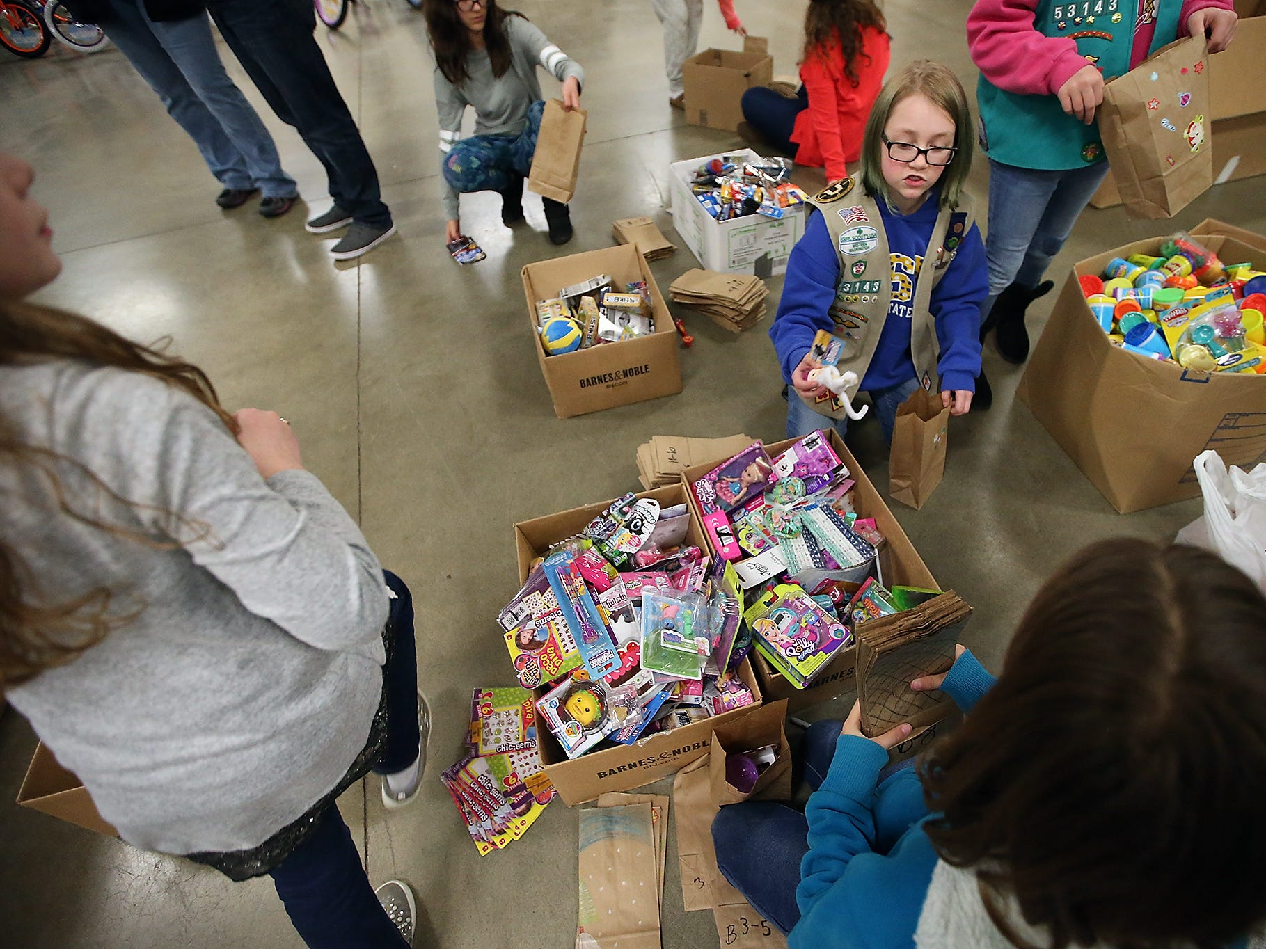 Girl Scout Rebecca Bolton, 12, and fellow young volunteers pack stocking stuffer bags to be given out during the upcoming Toys For Tots event in President's Hall at the Kitsap County Fairgrounds on Wednesday, December 12, 2018.