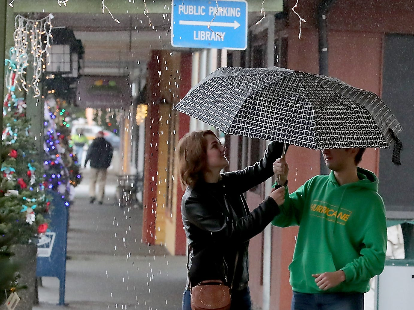 Danielle Hemphill reaches up to collapse the umbrella as she and brother Joel make it out of the rain and to the covered sidewalks of downtown Port Orchard on Thursday, December 13, 2018.