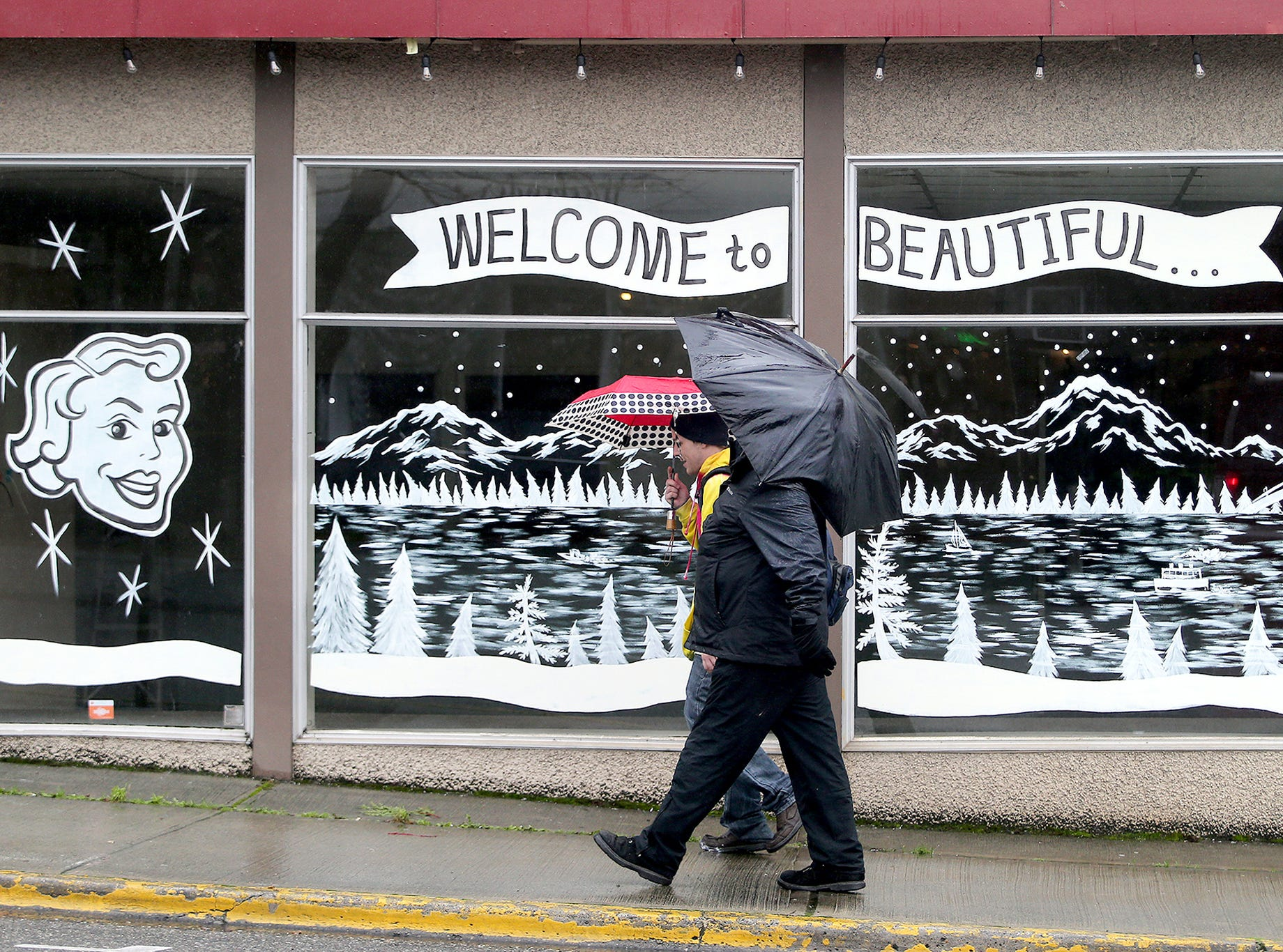 It's walking in a rainy wonderland in Bremerton on Thursday, December 13, 2018. Pedestrians walk past the former Manette TV building in Manette, under a snowy Olympics Mountains, and winter Manette view theme on the window.