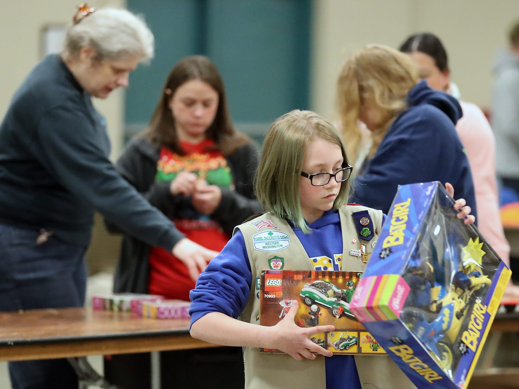 Girl Scout Rebecca Bolton, 12, carries a couple of newly sorted toys to the tables as she helps set up for the upcoming Toys For Tots event in President's Hall at the Kitsap County Fairgrounds on Wednesday, December 12, 2018.