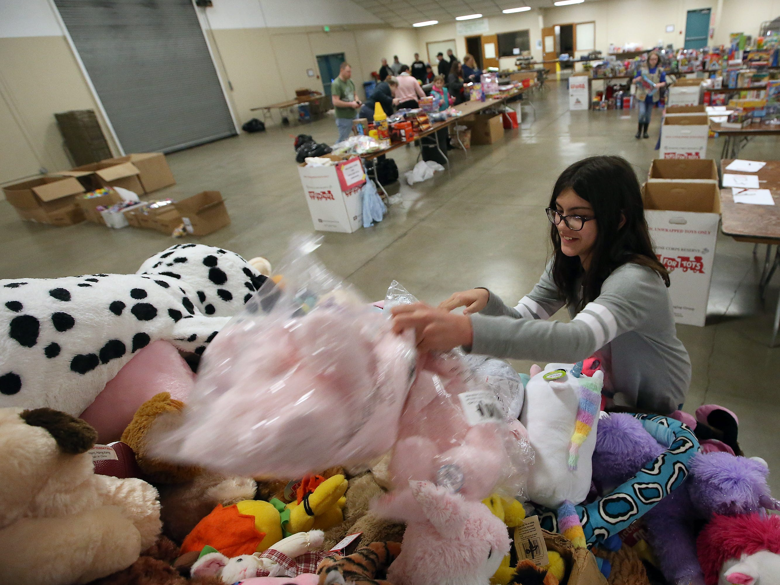 Hailey Hawk, 11, tosses a few teddy bears on to the top of the stuffed animal pile as she helps set up for the upcoming Toys For Tots event in President's Hall at the Kitsap County Fairgrounds on Wednesday, December 12, 2018. This is the second year that Hailey has helped out with the event.