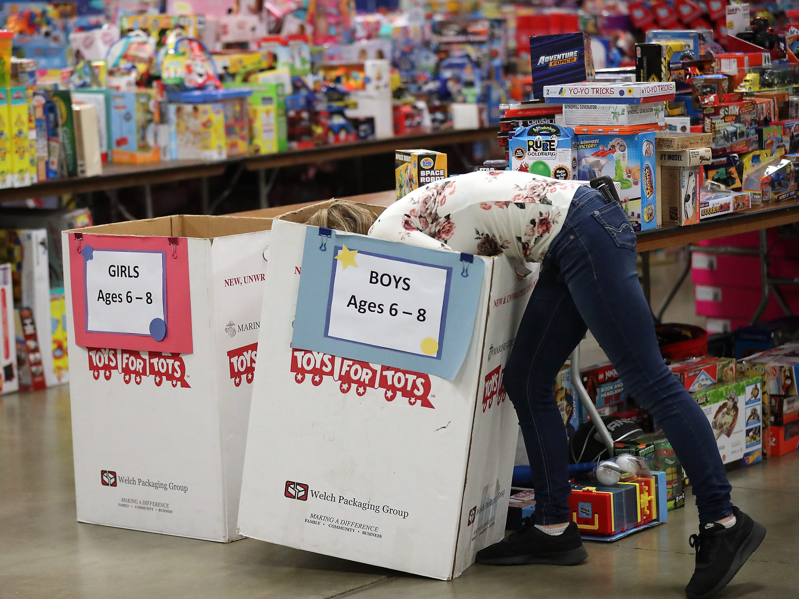 Volunteer Mikayla Hawk, 14, disappears halfway into a box as she grabs toys out of it to be displayed on tables during the preparation for the upcoming Toys For Tots event in President's Hall at the Kitsap County Fairgrounds on Wednesday, December 12, 2018.