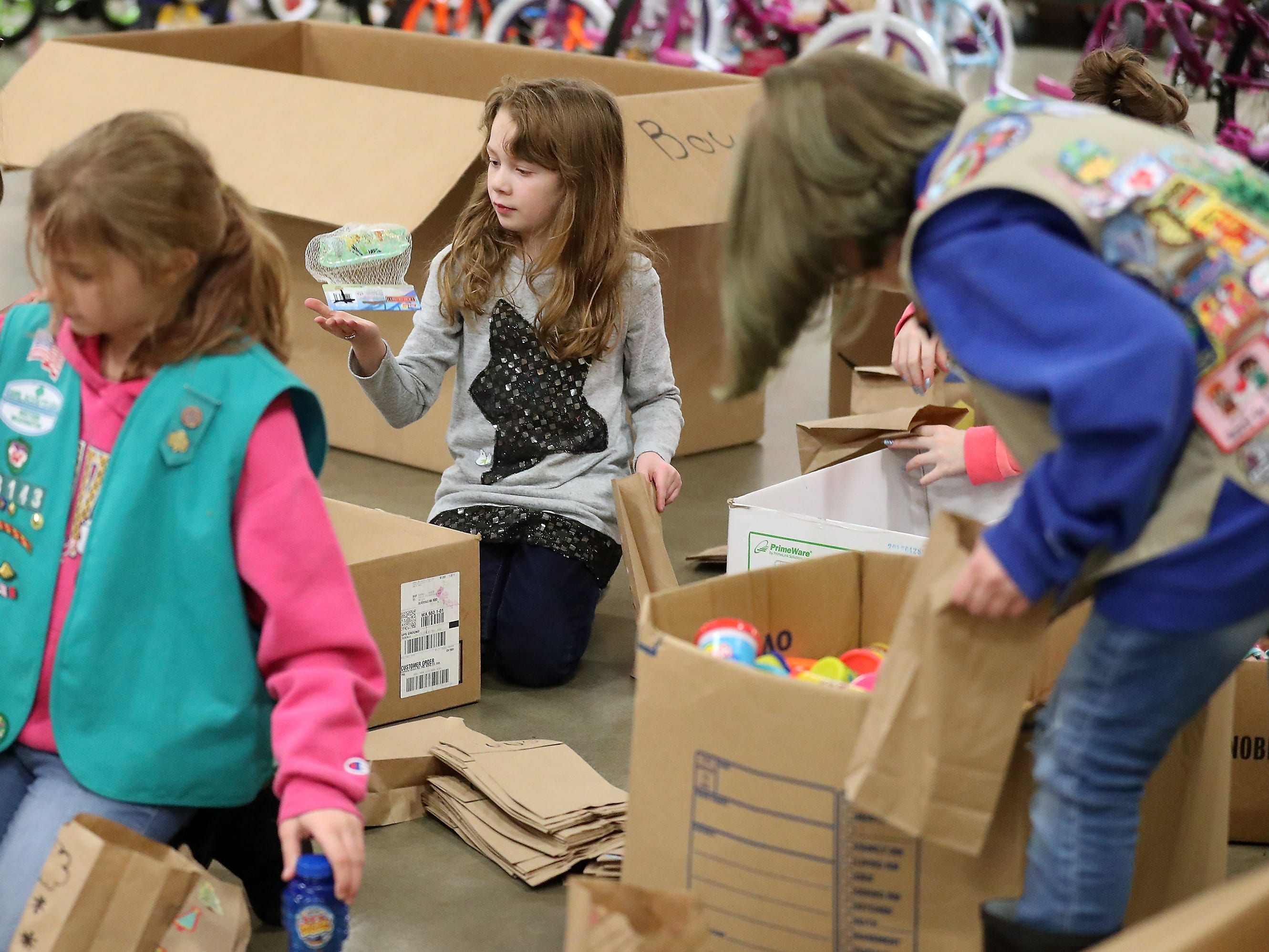 Lily Cogill, 9, (center) and fellow young volunteers help put together stocking stuffer bags to be given out during the upcoming Toys For Tots event in President's Hall at the Kitsap County Fairgrounds on Wednesday, December 12, 2018.