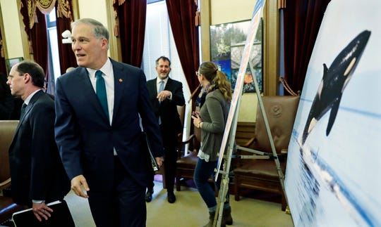 Washington Gov. Jay Inslee walks past a photo of an orca whale after he talked to reporters about his 2019-2021 budget proposal Thursday at the Capitol in Olympia.