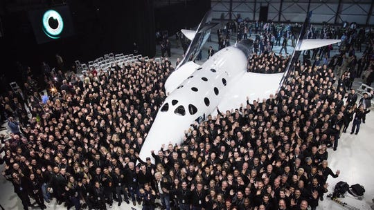 """Virgin Galactic's SpaceShipTwo """"VSS Unity,"""" surrounded by employees from The Spaceship Company, which built the spacecraft."""