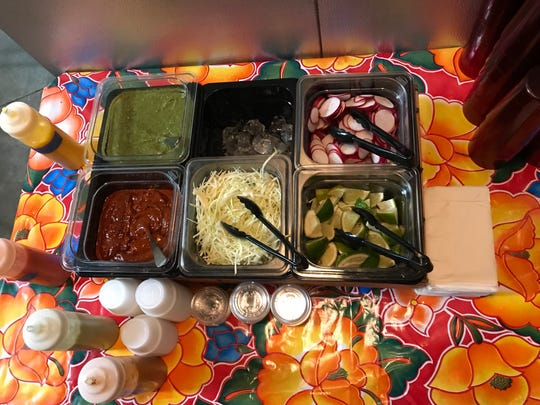 The available taco additions, including limes and an array of salsas.
