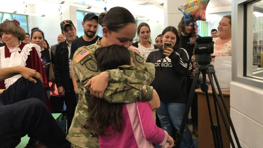 Army Sergeant First Class Irene Zepeda hugs her daughter, Miriam Lopez, as family record their reunion nearby. Zepeda returned from Afghanistan and surprised her daughter at Garcia Elementary School on Thursday, Dec. 13, 2018.