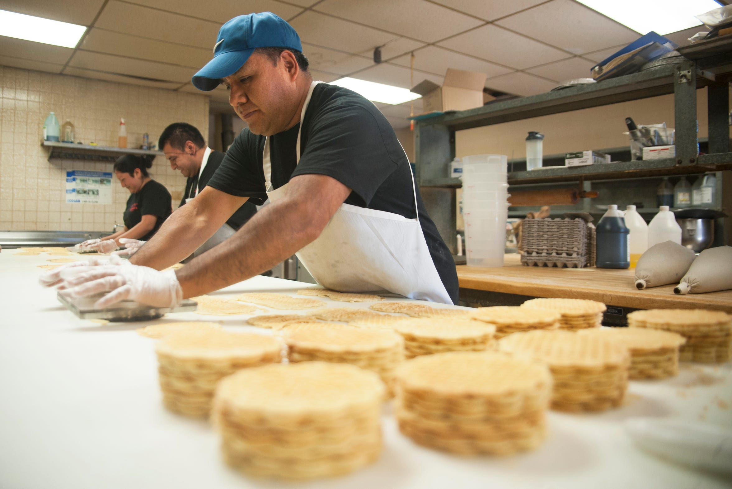 Chief baker Victor Regino, right, trims freshly baked pizzelle at Del Buono's Pizzelle Company in Bellmawr.