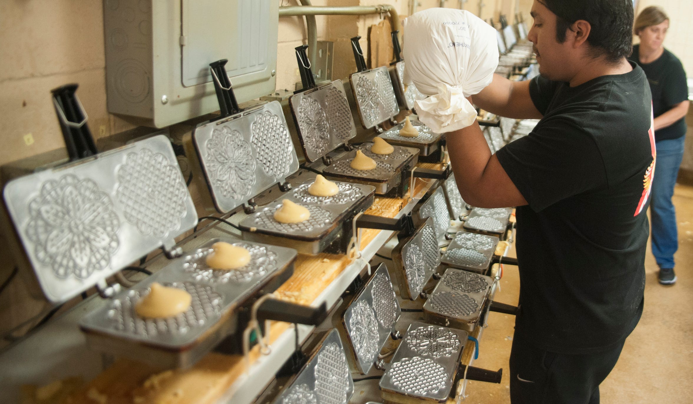 Baker Victor Christian Garcia loads batter into pizelle irons at Del Buono's Pizzelle Company in Bellmawr.