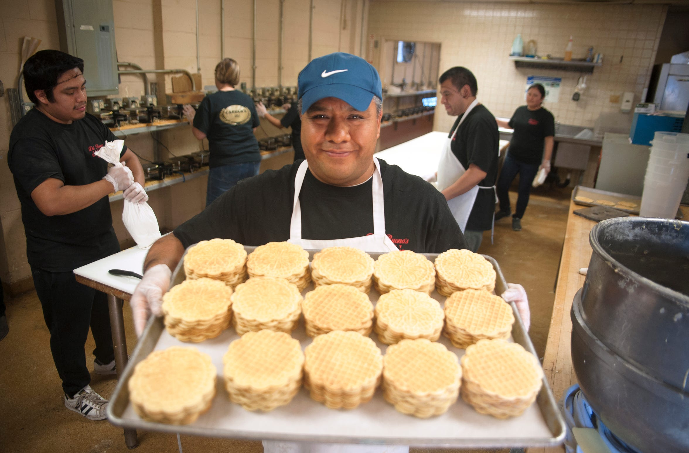 Chief baker Victor Regino displays a tray of freshly baked pizzelle at Del Buono's Pizzelle Company in Bellmawr.