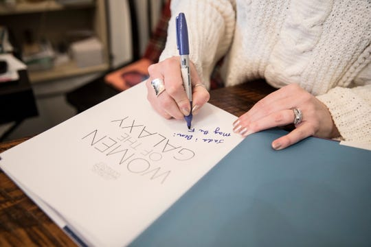 """Amy Ratcliffe signs one of the last remaining """"Star Wars: Women of the Galaxy"""" books that was reserved for a customer before she left Wheatberry Books on December 8, 2018."""