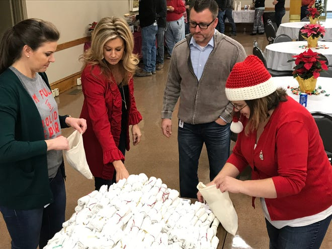 From left, Misty Tuttle, Debbie Bettendorf, Trevor Kendall and Sarah Brown add personal hygiene items to bags that will be distributed to school districts across the region.