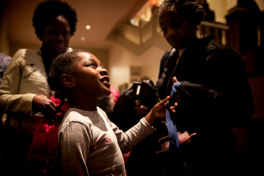 Martaisha Thomas, 7, listens to Julie Sunderland, the director of education and outreach at the Cincinnati Ballet, talk about Martaisha's ballet lessons that will start in January.