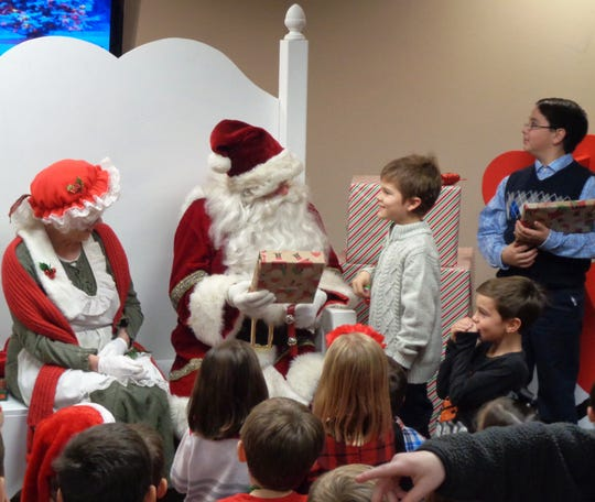 Santa Claus called every boy and girl by name to personally greet them with a gift during Christmas with Santa sponsored by the Knights of Columbus at St. Columban Church in Loveland.