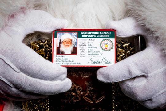 "Santa Kent holds his ""Worldwide Sleigh Driver's License"" in The Enquirer studio in Downtown Cincinnati Wednesday, December 12, 2018."