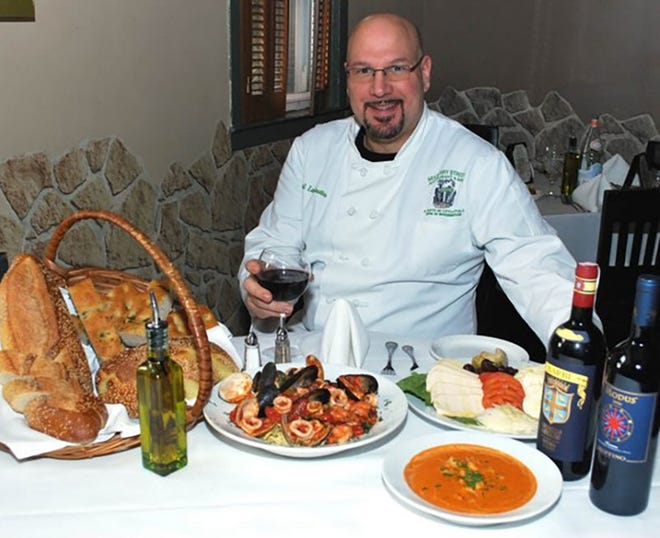Paul LaGrutta, owner-executive chef of Mulberry Street in Woodbridge, stands with part of the Feast of the Seven Fishes he will serve on Christmas Eve at his Rahway Avenue restaurant.