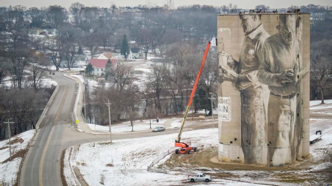 Guido van Helten works from his photos of local residents to finish a mural wrapped around a 110-foot silo Wednesday, Dec. 12, 2018, in Fort Dodge, Iowa. 