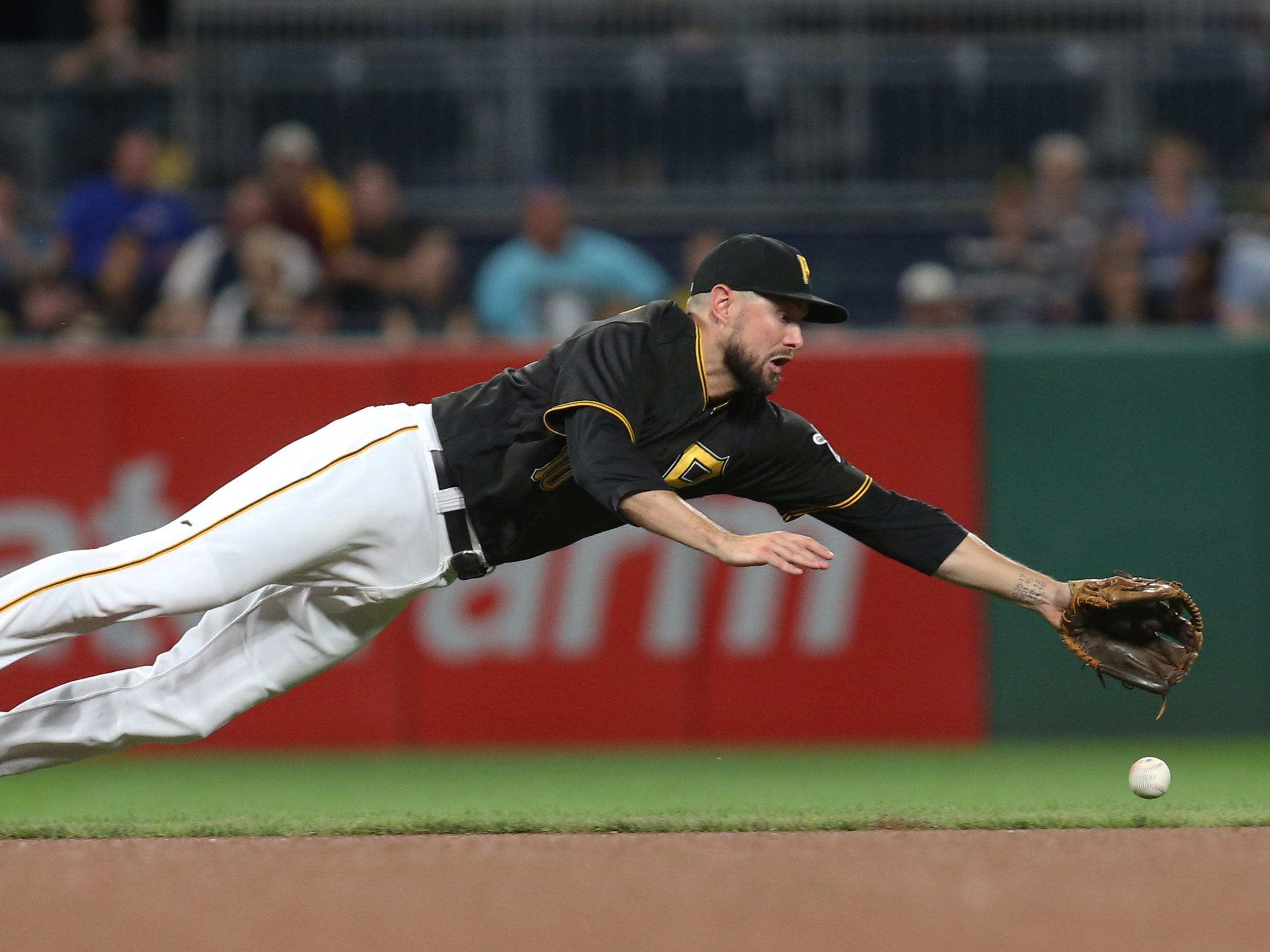 Pittsburgh Pirates shortstop Jordy Mercer dives for a ground ball against the Miami Marlins in the fourth inning at PNC Park, Sept. 7, 2018.