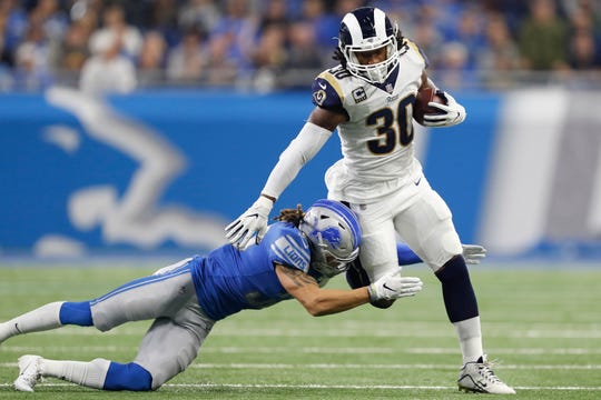 Los Angeles Rams running back Todd Gurley runs against Detroit Lions cornerback Mike Ford at Ford Field, Dec. 2, 2018.