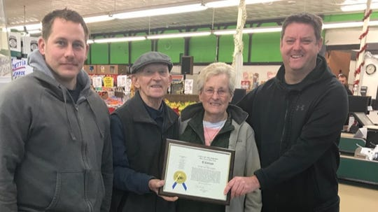 Dearborn firefighter Adam Ferrell (far left) and Capt. Steve Worden (far right) present Art Hughes and his wife Ellen a citation from Dearborn Mayor O'Reilly recognizing their efforts at the Dearborn Farm Market, a week before the market's sale was announced on Dec. 12, 2018.