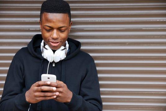 Teenage Boy Listening To Music And Using Phone