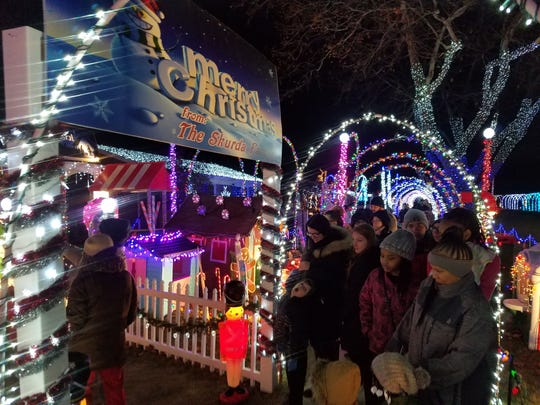 A crowd of people walk through the display of holiday decorations on Eiffel Avenue in Warren