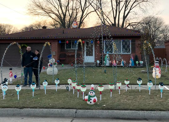 Chris and Heather Goode of Warren with the lighted hoop decorations on the sidewalk in front of their house on Dec. 13, 2018 — Christmas decorations they put up that earlier this month prompted a violation letter from a Warren city inspector.