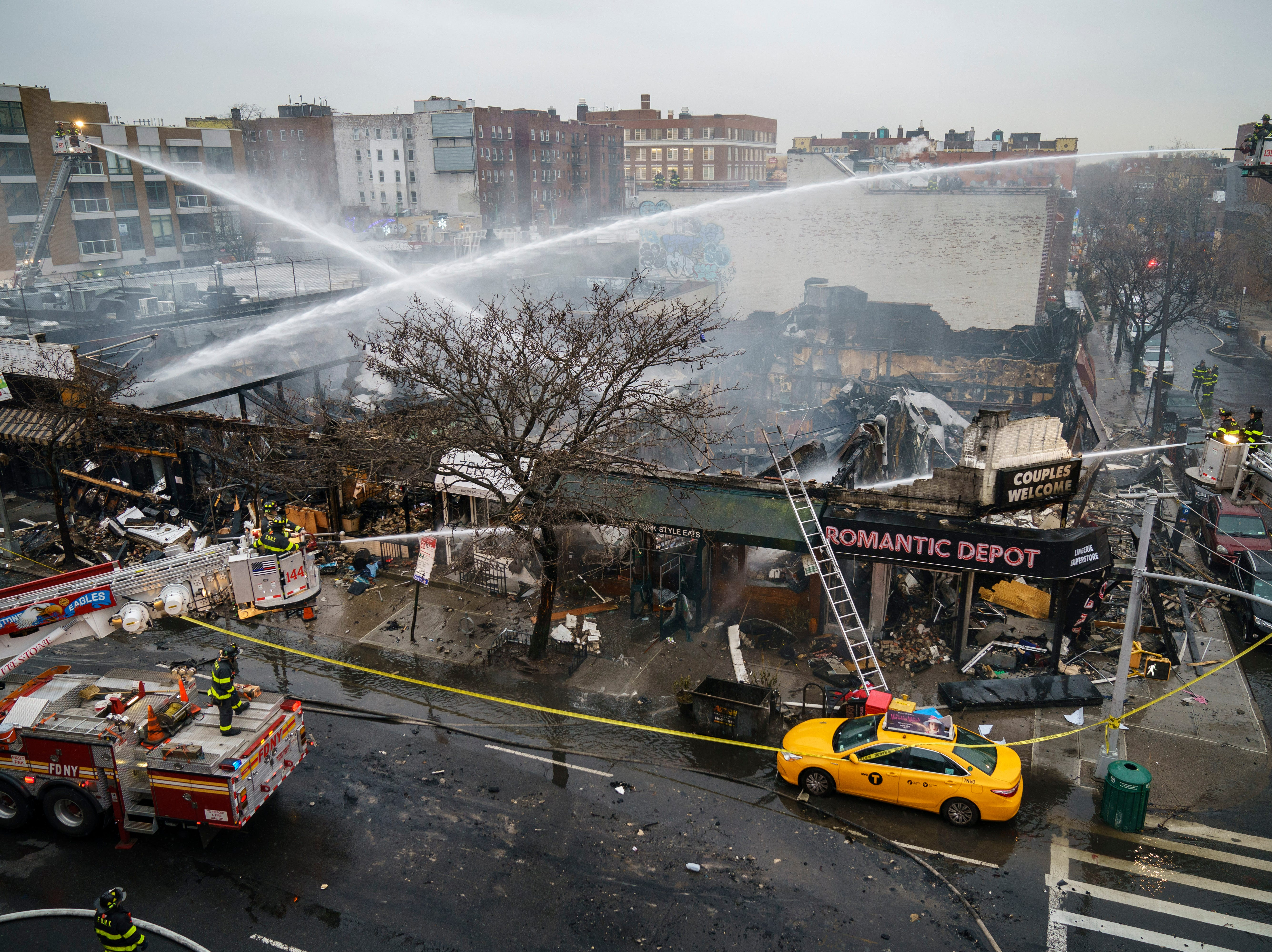 Firefighters work to put out the smoldering remains of an overnight fire that engulfed six businesses on Queens Boulevard, Dec. 13, 2018 in the Queens borough of New York City. A dozen people were injured, including six firefighters. The cause of the fire is still under investigation.