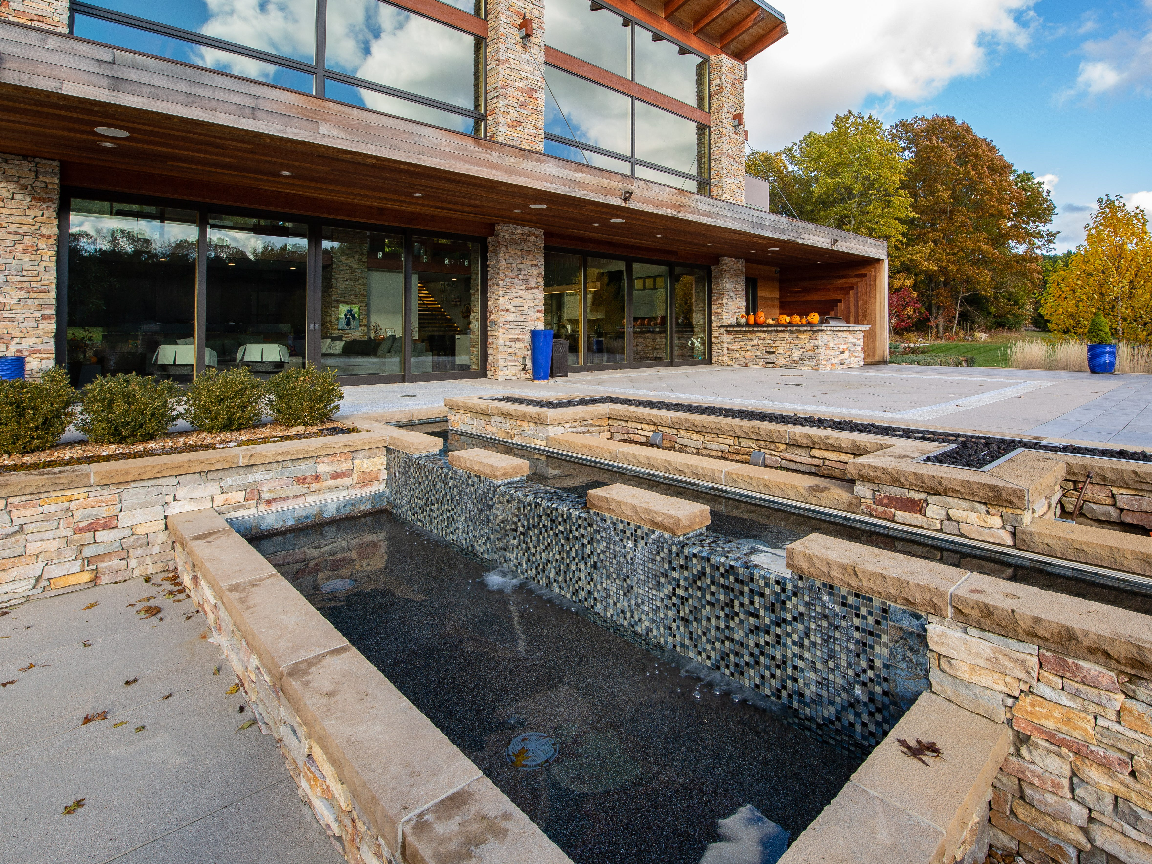 The stone, stucco and wood-sided home has two hot tubs and an in-ground swimming pool with a slide on an outdoor patio.