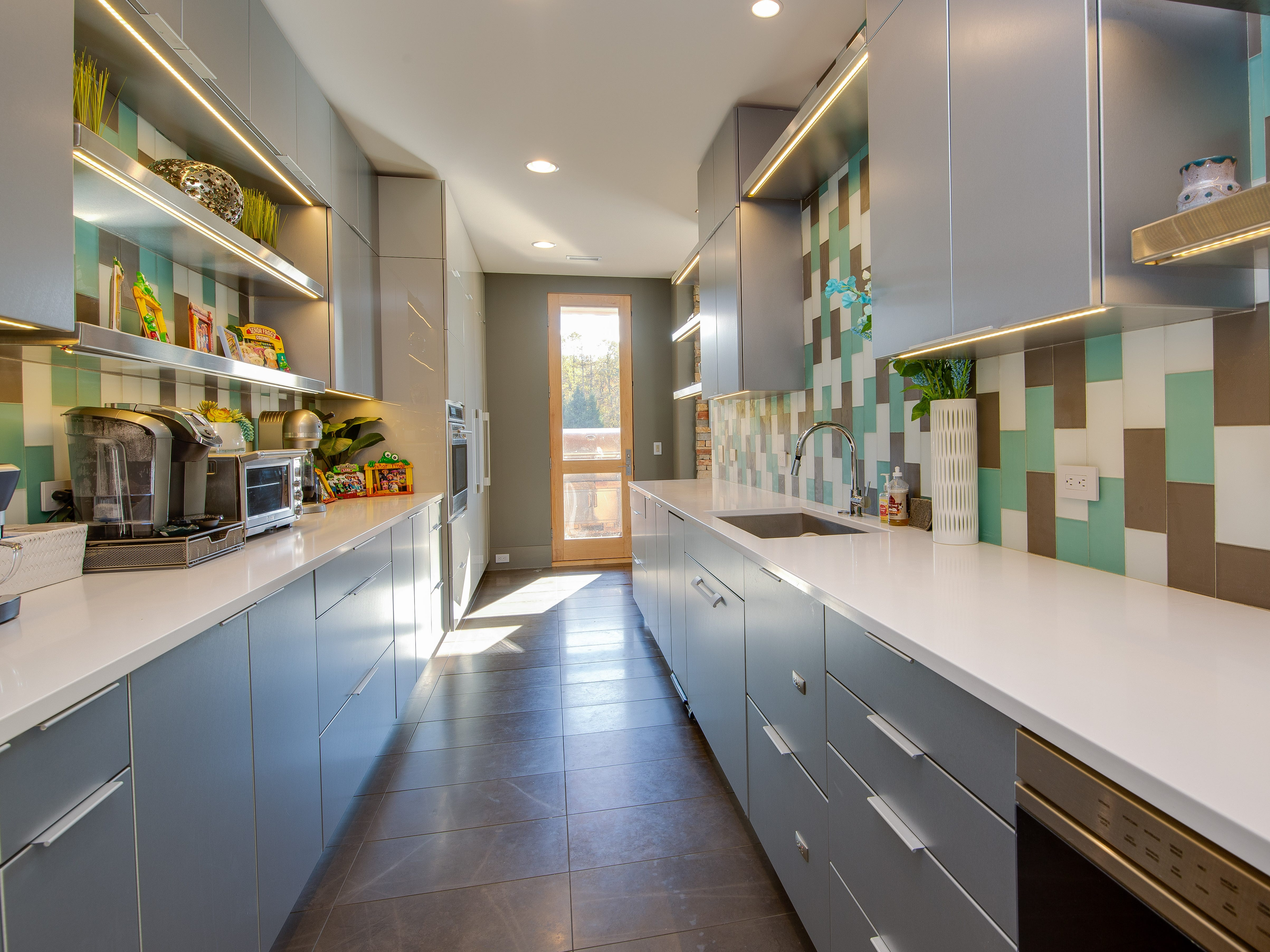 An adjoining prep kitchen with pantry and wine dispenser.