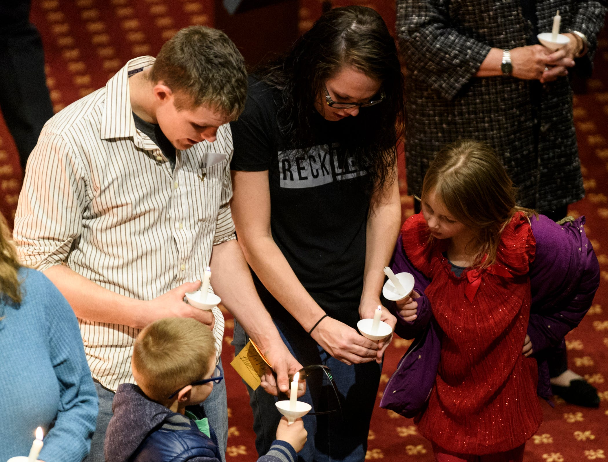 Zachary Herron, center left, and Leann Herron, center right, help their children Kaleb, 5, left, and Karen, 7, right, light candles as they stand in a large circle around the sanctuary of Trinity United Methodist Church during the 18th annual Homeless Memorial service organized by Aurora, a local non-profit serving area's homeless population, in downtown Evansville, Ind., Tuesday, Dec. 11, 2018.